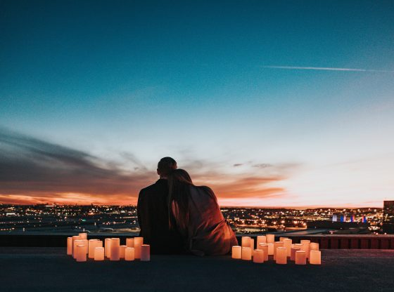 couple sitting on roof with lanterns