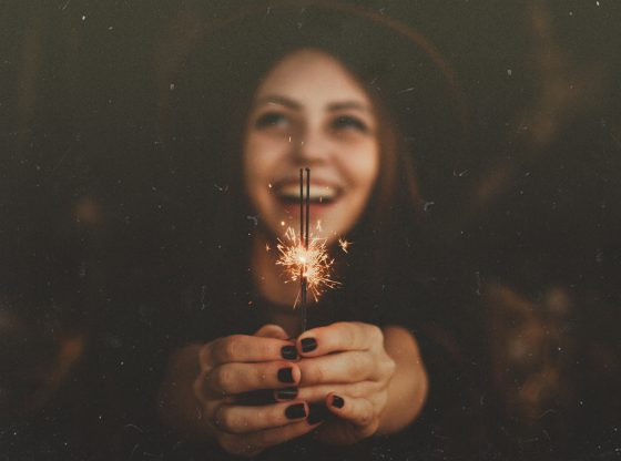 happy woman holding sparkler