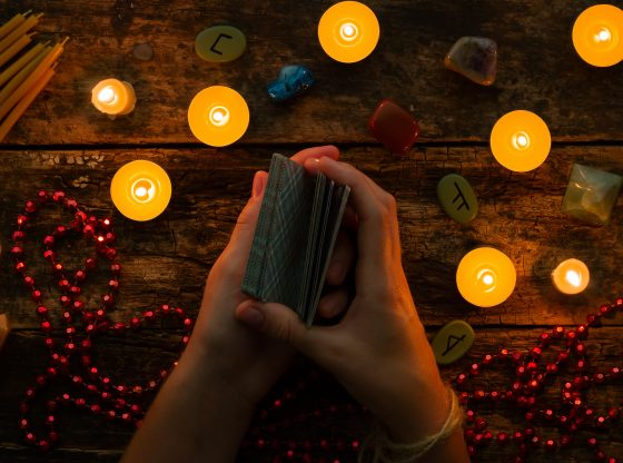 hands holding tarot cards by candlelight