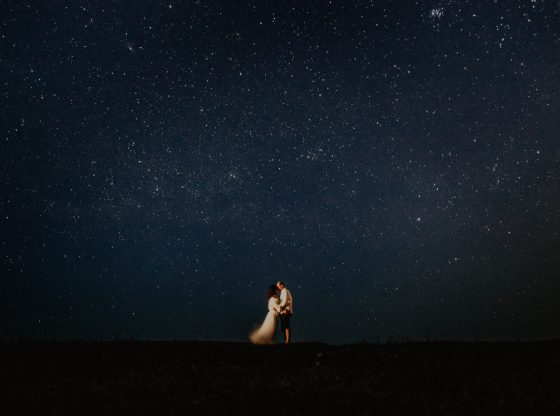 man and woman standing under the night sky