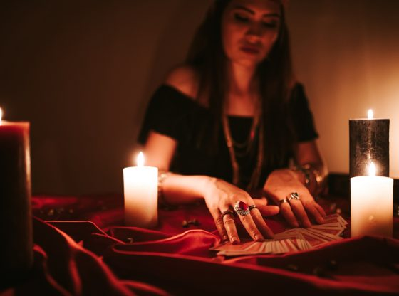 Young female fortune teller is looking into tarot cards