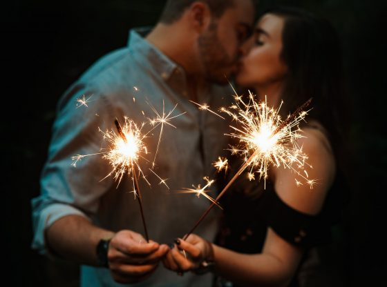 couple holding sparklers and kissing