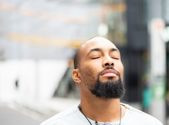 African American man closing eyes and feeling serene