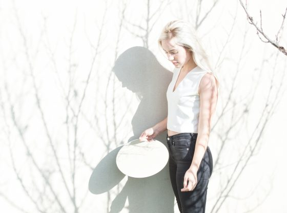 A person is performing shadow work holding a mirror.